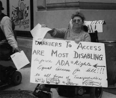 larger photo of Luda demonstrating for accessible taxis
