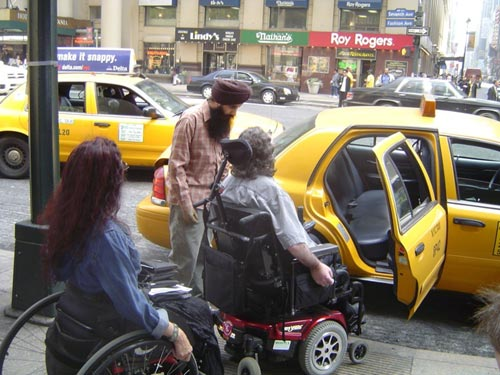 larger photo of two people in wheelchairs in front of a cab