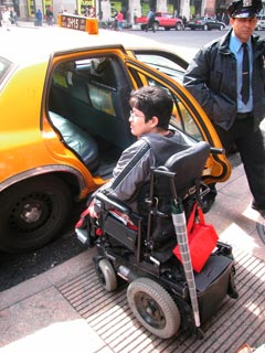 larger photo of a woman in a wheelchair in front of an open taxi door