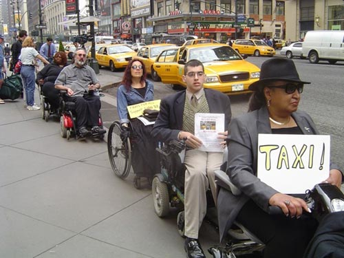 larger photo of people in wheelchairs waiting for cabs