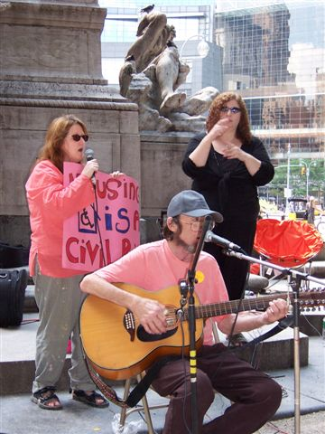 larger photo of Disabled In Action Singers, including Eric Levine, and a sign language interpreter