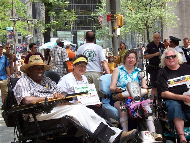 another larger photo of activists gathering at Rockefeller Center, such as Joseph Skeete, Jean Ryan and Michael Costello