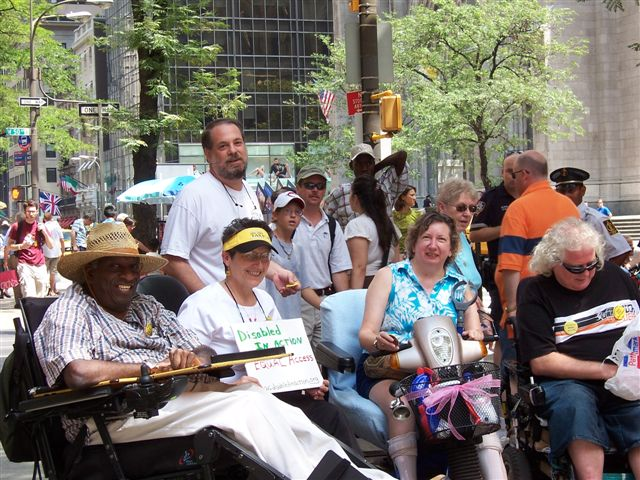 larger photo of activists gathering at Rockefeller Center, such as Joseph Skeete, Jean Ryan and Michael Costello