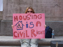 photo of a woman holding up a pink sign reading Housing Is A Civil Right
