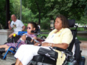photo of a couple of disabled people in wheelchairs listening to speeches