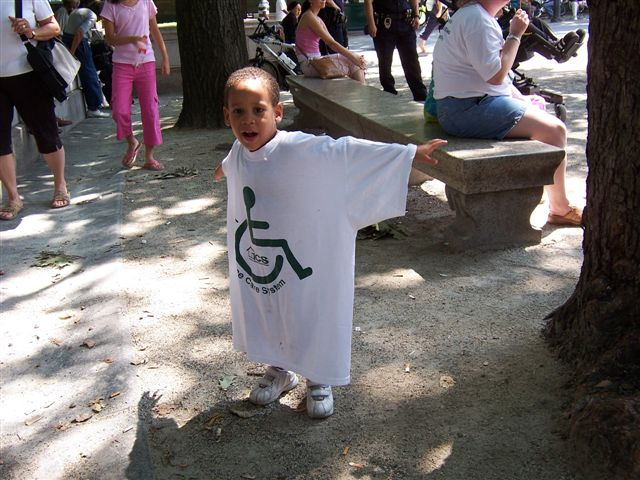 larger photo of a young boy in an ICS T-shirt stretching his arms out wide