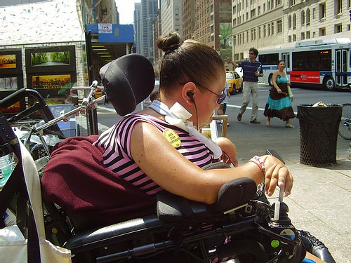 larger photo of a woman in a wheelchair on the sidewalk