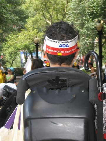 larger photo of back view of person's head wearing a sign proclaiming the ADA