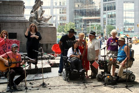 larger photo of activists singing at ADA rally