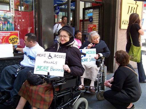 larger photo of a female activist in a wheelchair holding a sign reading More Access Equals More Business