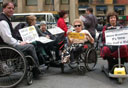 photo of two people in wheelchairs in front of a cab