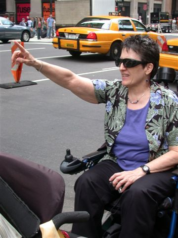 larger photo of Jean Ryan from her wheelchair with right arm in the air
