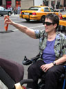 Jean Ryan from her wheelchair with right arm in the air hailing a cab