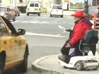 Photo of Jean Ryan in a scooter trying to hail a cab