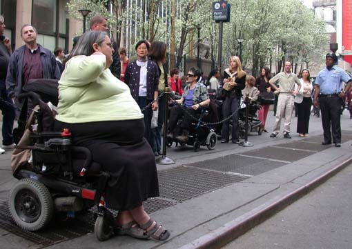 larger photo of people in wheelchairs and pedestrians at Penn Station taxi stand