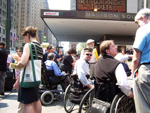 larger photo of people in wheelchairs talking to reporters in front of Madison Square Garden