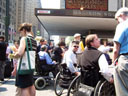 photo of people in wheelchairs talking to reporters in front of Penn Station