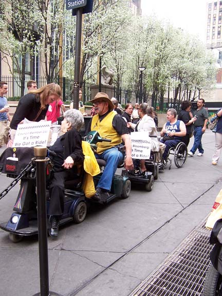 larger photo of people in wheelchairs and electric scooters at Penn Station taxi stand