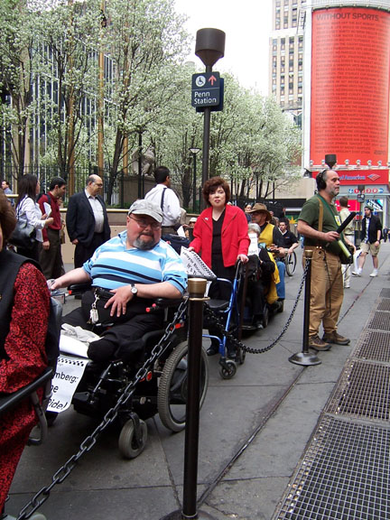 larger photo of people in wheelchairs and others using walkers at Penn Station taxi stand