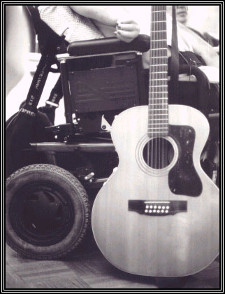 Photo of guitar next to a motorized wheelchair
